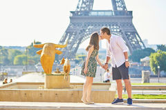Young romantic couple kissing near the Eiffel tower Royalty Free Stock Images