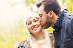 Young romantic couple kissing in the park in autumn Stock Photos