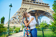 Young romantic couple kissing under the Eiffel tower Royalty Free Stock Image