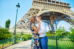 Young romantic couple kissing under the Eiffel tower Royalty Free Stock Images