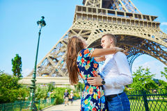Young romantic couple kissing under the Eiffel tower. Young romantic couple kissing with passion near the Eiffel tower in Paris, France stock photo