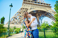 Young romantic couple kissing under the Eiffel tower Royalty Free Stock Photo