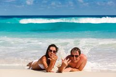 Young romantic couple laying on sandy beach Royalty Free Stock Photography