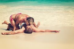 Young romantic couple laying on sandy beach Stock Photography