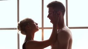 Young romantic couple looking at each other indoor. Portrait of a sensual couple in love embracing while standing and looking at each other. Beautiful stock video footage