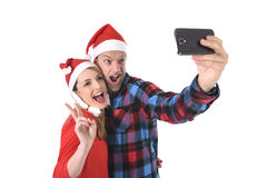 Young romantic couple in love taking selfie mobile phone photo at Christmas. Christmas young beautiful couple in Santa hats in love taking romantic self portrait Stock Photo