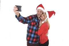 Young romantic couple in love taking selfie mobile phone photo at Christmas. Christmas young beautiful couple in Santa hats in love taking romantic self portrait Royalty Free Stock Photography
