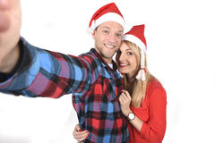 Young romantic couple in love taking selfie mobile phone photo at Christmas. Christmas young beautiful couple in Santa hats in love taking romantic self portrait Royalty Free Stock Image