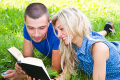 Young romantic couple lying in park and reading Royalty Free Stock Images