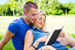 Young romantic couple lying in park and reading Royalty Free Stock Photo