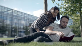 Young romantic couple lying in park and reading book. stock video