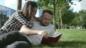 Young romantic couple lying in park and reading book. stock video footage