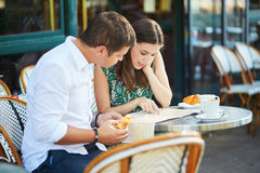Young romantic couple with map in French cafe Royalty Free Stock Photo