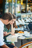 Young romantic couple with map in French cafe Stock Image