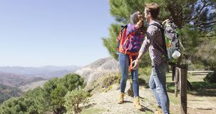 Young romantic couple in mountains. Young male giving flower to woman while both hiking with backpacks in mountains in summer time stock video footage