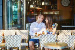 Young romantic couple in Parisian cafe Stock Images