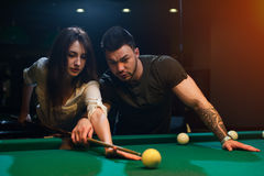 Young romantic couple playing snooker in club Royalty Free Stock Images