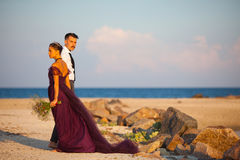 Young romantic couple relaxing on the beach watching the sunset Stock Image