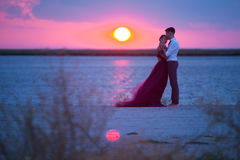 Young romantic couple relaxing on the beach watching the sunset Royalty Free Stock Photo