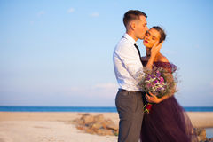 Young romantic couple relaxing on the beach watching the sunset Stock Photography