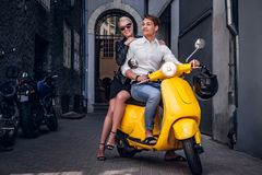 Romantic couple riding on vintage Italian scooter in the old narrow street of Europe. Young romantic couple riding on vintage Italian scooter in the old narrow stock photography