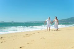 Young romantic couple running on the beach holding hands Stock Photo