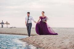 Young romantic couple running on the beach of sea. The wedding day at the sea. Young romantic couple running on the beach Royalty Free Stock Photo