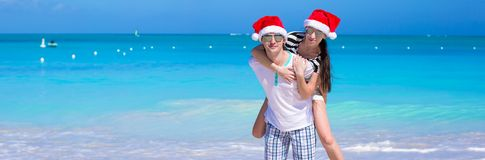 Young romantic couple in Santa hats during beach Royalty Free Stock Images
