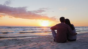 Young romantic couple sitting on the beach, admiring the sunset. Back view stock footage