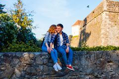 Romantic couple sitting on a wall near the castle. Young romantic couple sitting embracing on a wall near the Uzhhorod castle. Historical places of interest in royalty free stock photos