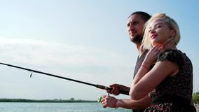 Young romantic couple sitting and fishing together on dock by riverside, lovers fishing in sunbeam stock video footage