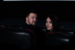 Young romantic couple sitting in movie theater. Royalty Free Stock Photography