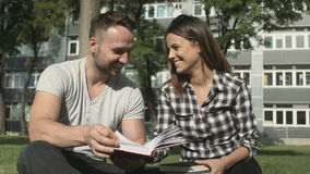 Young romantic couple sitting in park and reading book. stock video