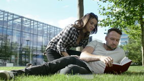 Young romantic couple sitting in park and reading book. stock footage