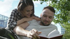 Young romantic couple sitting in park and reading book. stock video footage