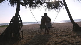 Free Young Romantic Couple Sitting Together On Swing At The Tropical Sea Beach And Hugging. Pair In Love Relaxing And Kissing Stock Image - 97351521