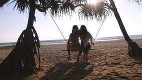 Young romantic couple sitting together on swing at the tropical sea beach and hugging. Pair in love relaxing and kissing Stock Images