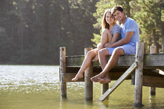 Young Romantic Couple Sitting On Wooden Jetty Looking Out Over L Royalty Free Stock Images