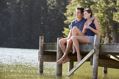 Young Romantic Couple Sitting On Wooden Jetty Looking Out Over Lake Royalty Free Stock Image
