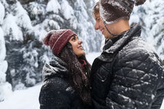Young Romantic Couple In Snow Forest Outdoor Man And Woman Embrace. Winter Pine Woods Stock Photos