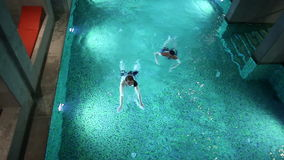 Young romantic couple swimming and relaxing in swimming pool stock video