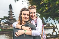 Young romantic couple of trourists on the Ulan Danu temple background. Bali island. Indonesia stock photo