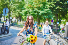 Young romantic couple using bicycles in Paris, France Stock Images