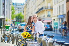 Young romantic couple using bicycles in Paris, France Royalty Free Stock Image