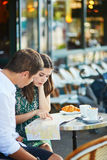 Young romantic couple using map in a cozy outdoor cafe in Paris, France Royalty Free Stock Photography