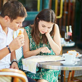 Young romantic couple using map in a cozy outdoor cafe in Paris, France Royalty Free Stock Image