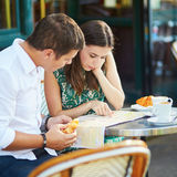 Young romantic couple using map in a cozy outdoor cafe in Paris, France Royalty Free Stock Photo