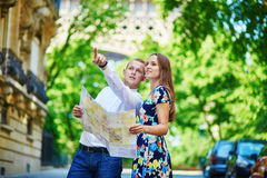Young romantic couple using map in Paris, France Stock Images