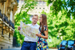 Young romantic couple using map in Paris, France Royalty Free Stock Photo