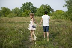 Young romantic couple walk in the field by the hands and laugh in the spring. Couple in white walking outdoors holding hands smili stock images
